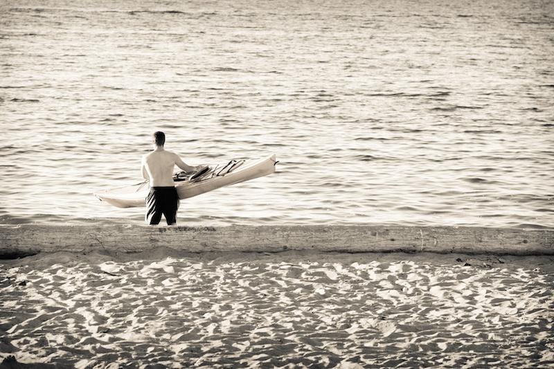 Young man walking kayak down to water at sunset