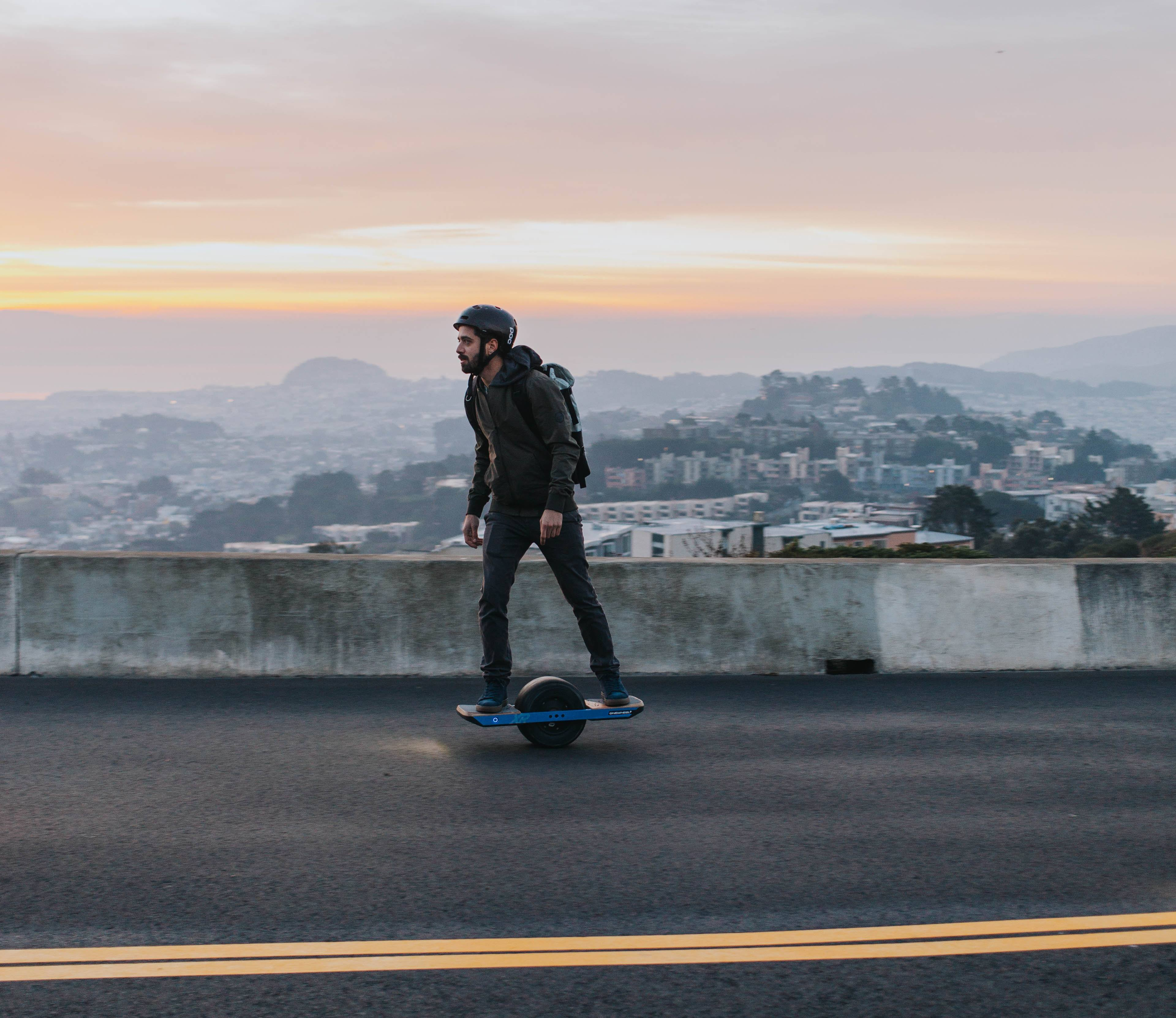 Man riding one wheel board on mountain