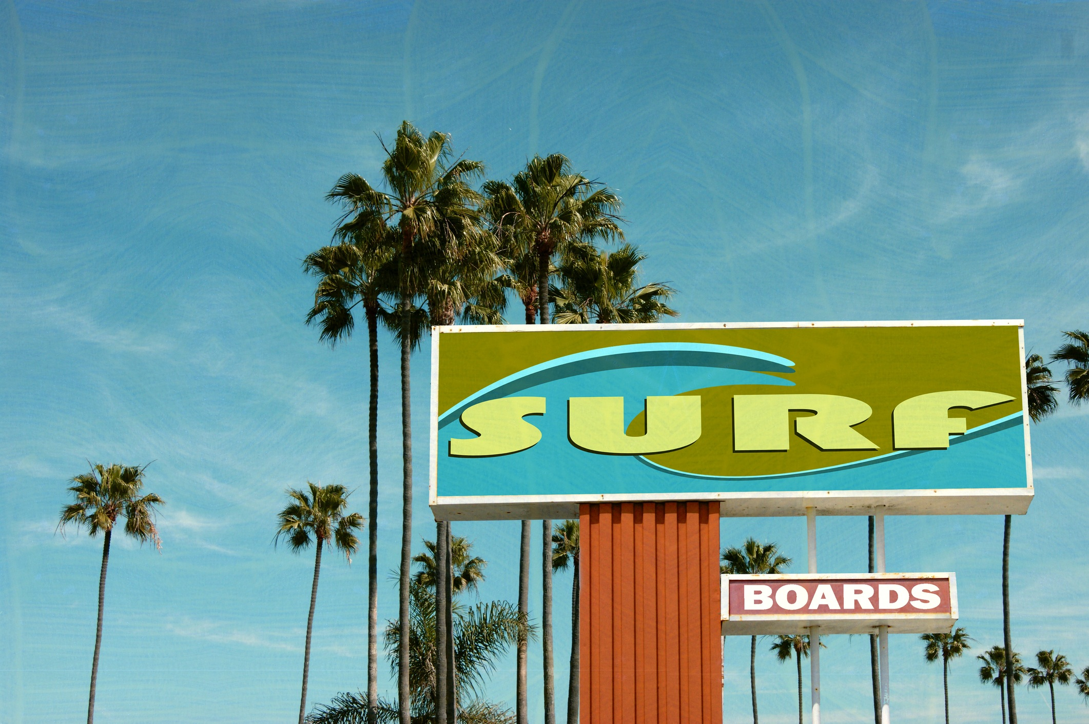 aged and worn surf sign on beach with palm trees