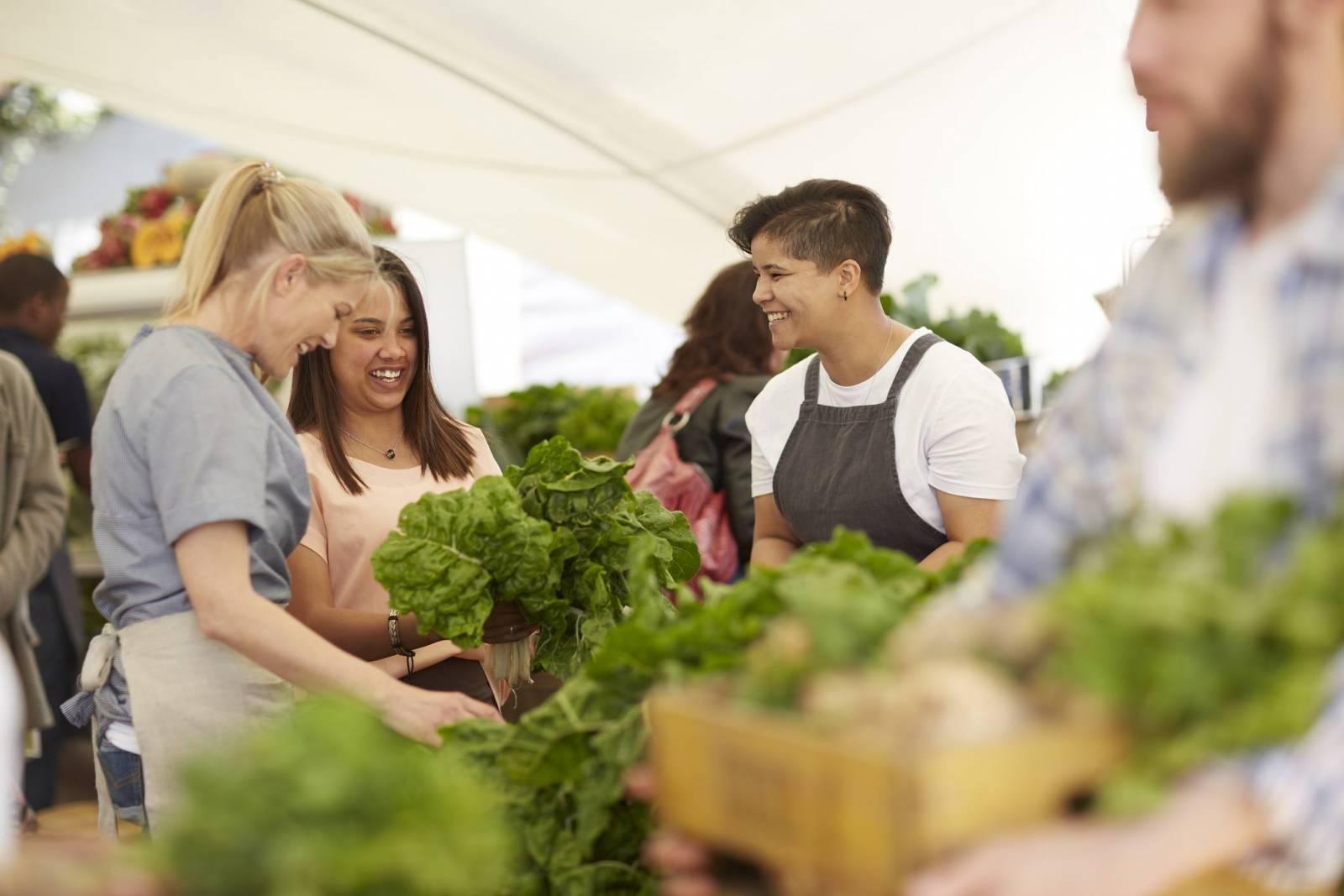 Women working, arranging vegetables at farmer's market