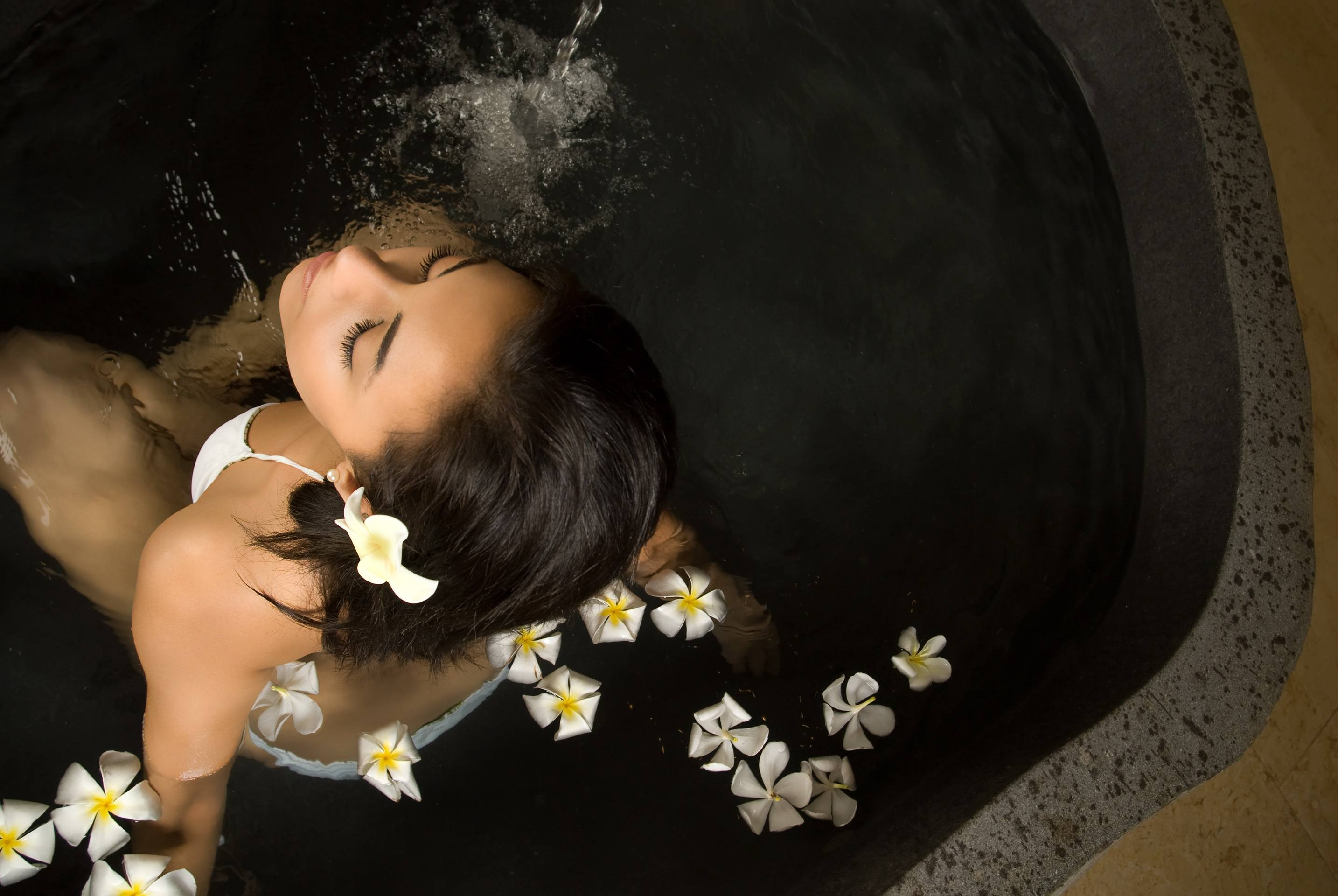 Woman relaxing in spa with floating white plumeria flowers
