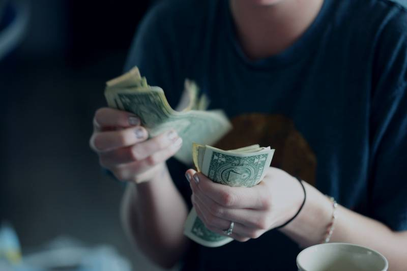 woman counting cash dollars