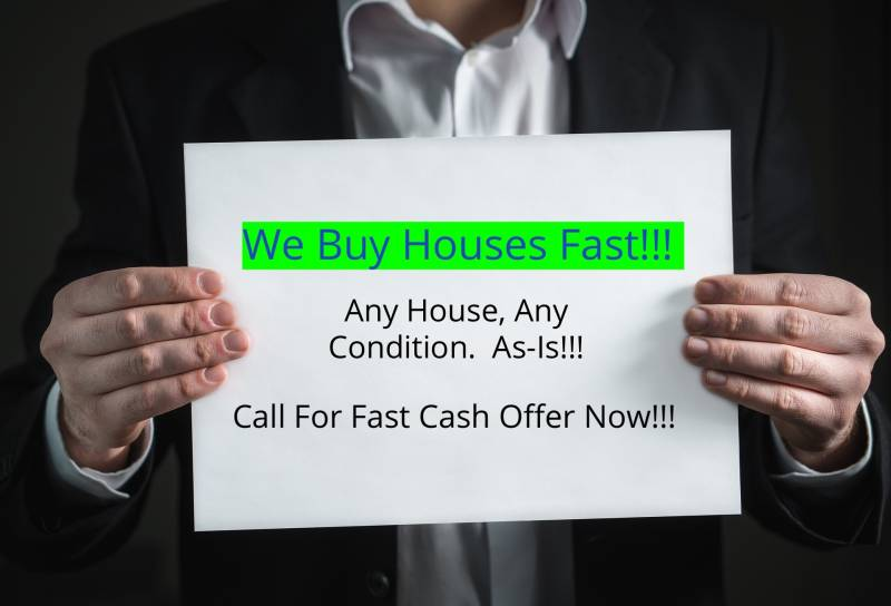 Man holding we buy house fast sign