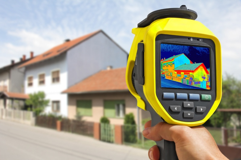 Man holding device measure heat loss of house