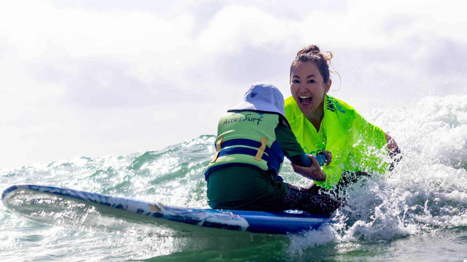 accesssurf volunteer and child on a wave