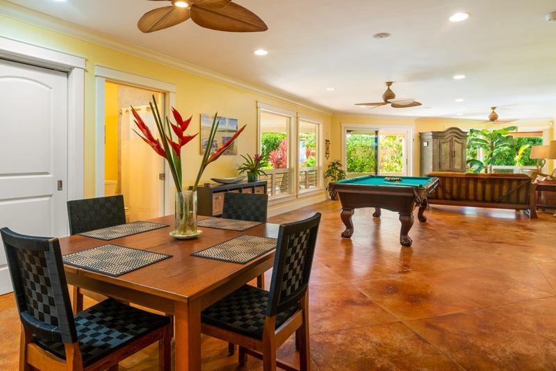The game room -- a dining table and chairs in the foreground and pool table in the background.