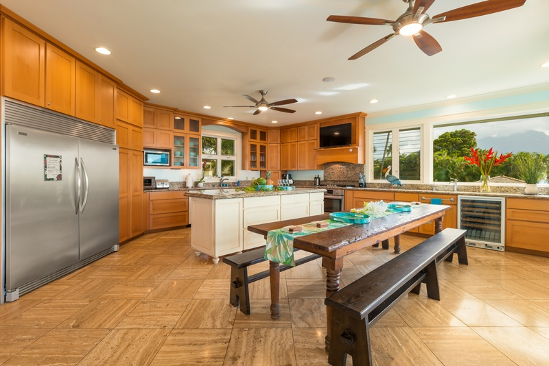 The kitchen - showing the large refrigerator, a large dining table with seating benches, and a kitchen island.