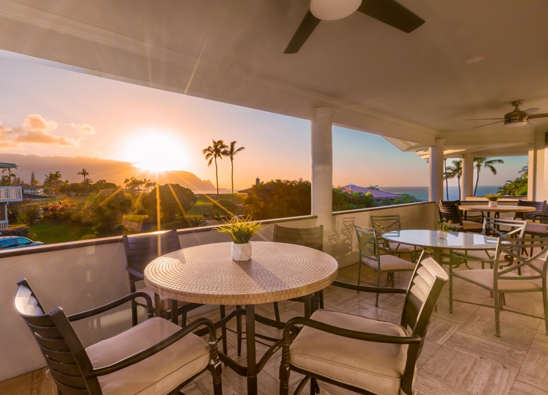 A table and chairs on the lanai, with the sun setting in the background.
