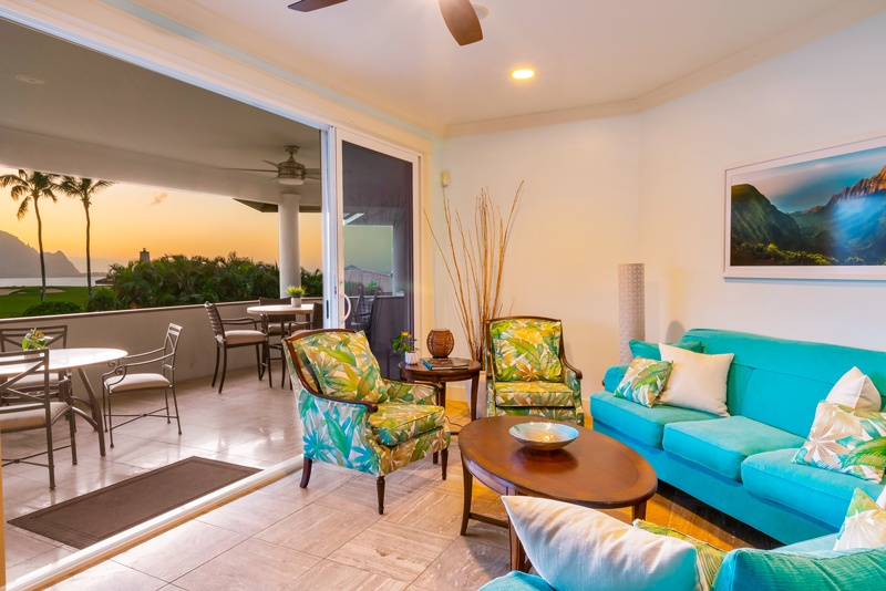A living area with a sofa and some chairs, the lanai in the background and the view of the ocean and palm trees.