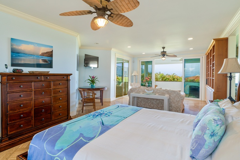 Bedroom photo -- showing the bed and a tropical ceiling fan, and a sitting area in the background and the lanani and view beyond.