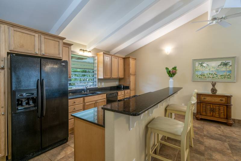 The kitchen with granite counters, and a large refrigerator.