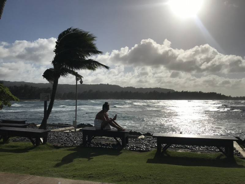 woman sits on bench on oahu beach
