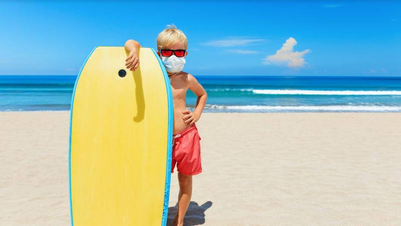 boy wearing face mask on kauai beach