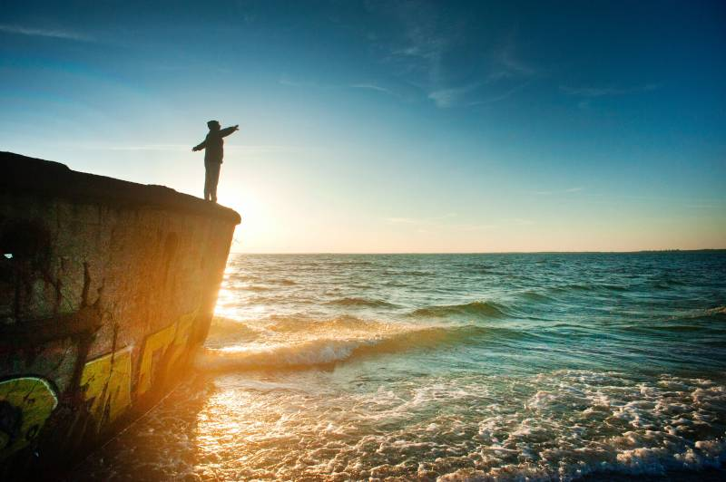 man standing on cliff over ocean