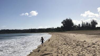 child runs down kauai beach