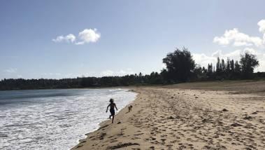 child runs down kauai beach