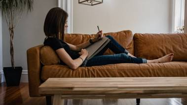 woman writing on notebook on brown sofa