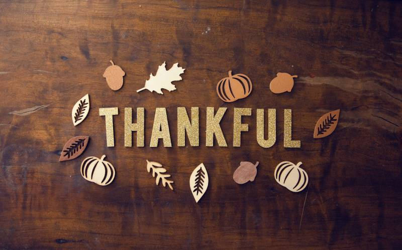 thankful in glitter letters with paper pumpkins and leaves