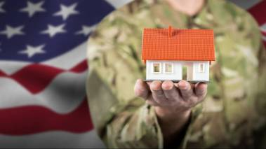 military member holding toy house