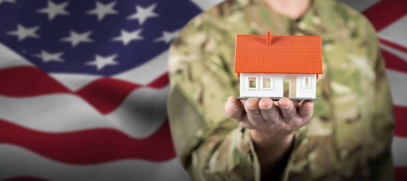 military person holding toy house