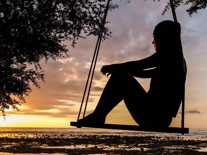 silhouette of woman on swing by oahu ocean