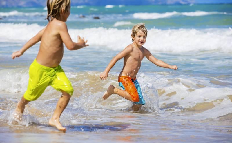 kids splash in waves on Maui beach