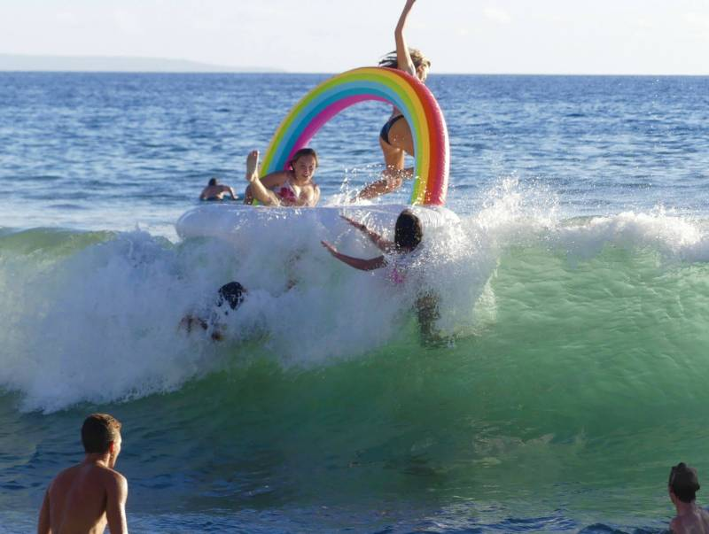 kids playing on inflatable rainbow in maui ocean