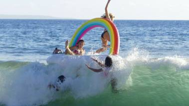 kids playing on inflatable pool in maui ocean