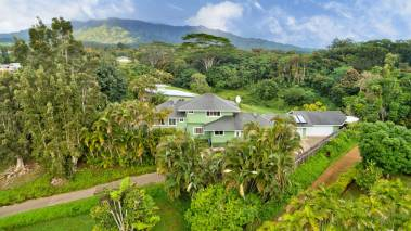 home for sale with lush tropical garden