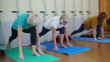 three older women doing yoga