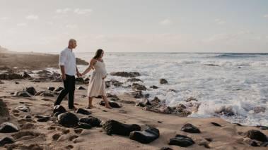 couple walks on hawaii beach at sunset