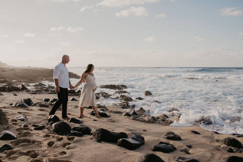 pregnant couple walks on oahu beach at sunset