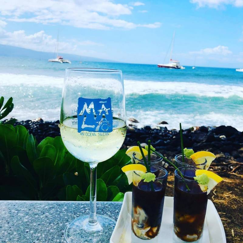 Glass of wine and oyster shooters with a view at Mala