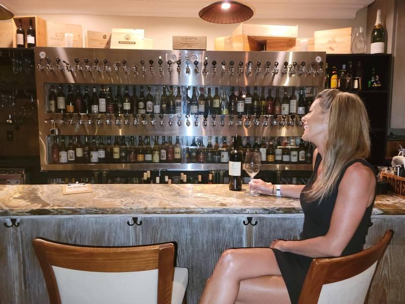 Girl laughing at Matteo's bar, enjoying wine on Maui