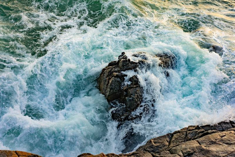 waves crash onto lava rocks on big island hawaii