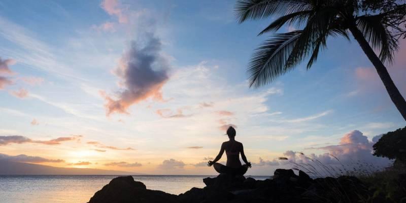 meditating at sunrise on the beach in hawaii