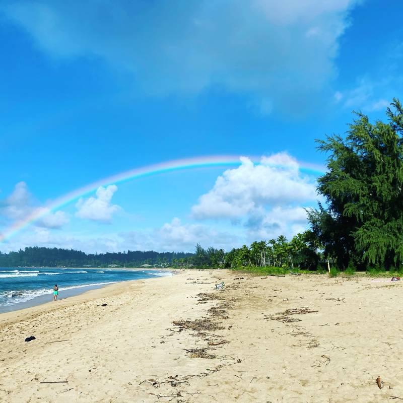 rainbow over north shore kauai beach