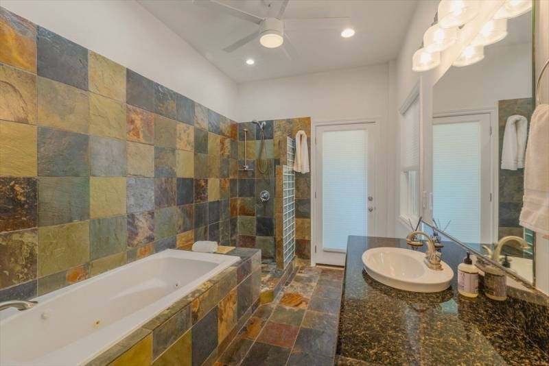 bathroom with slate tile shower and tub