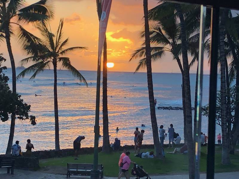 Crowd on beach at sunset in hawaii