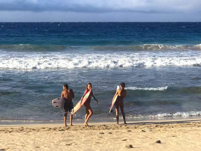 surfers on the beach on maui