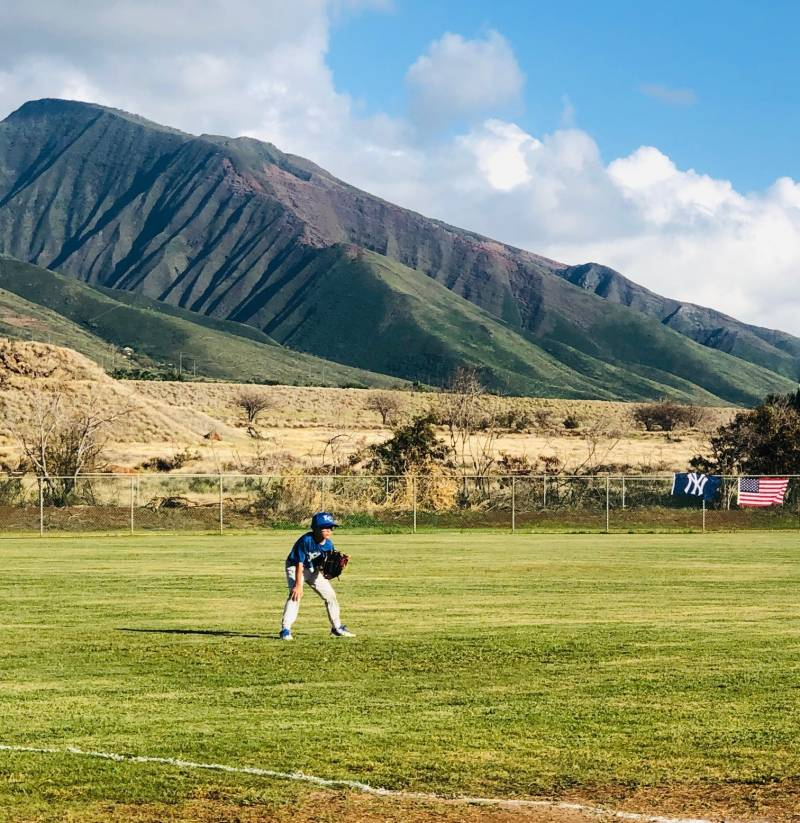 kid playing baseball in front of maui mountains