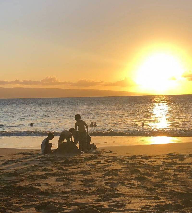kids play on beach during sunset on maui