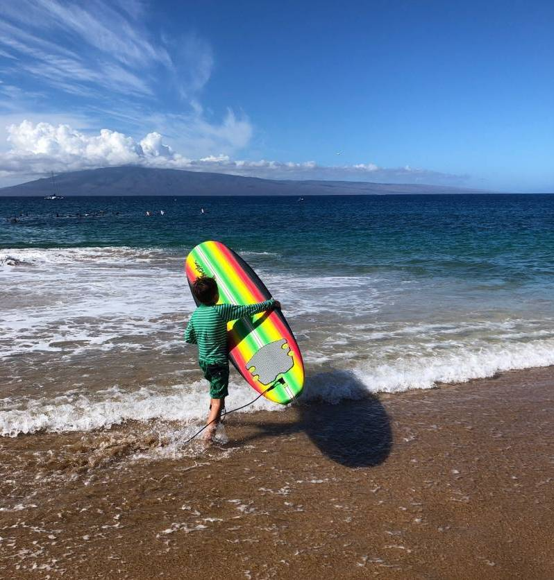 child with board on maui beach