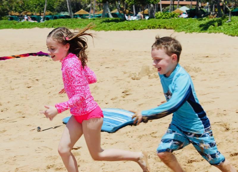 children play on beach in maui
