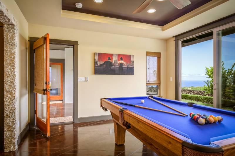 billiards room with large windows looking out to the ocean