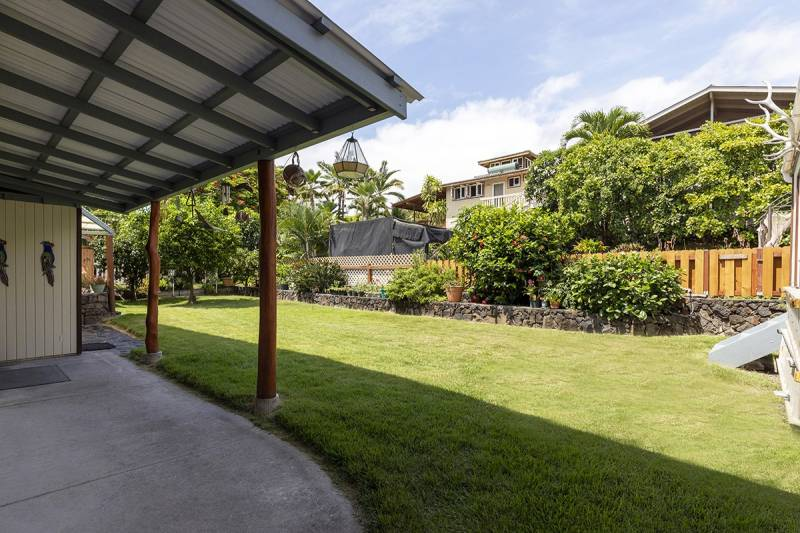 covered patio and grassy yard