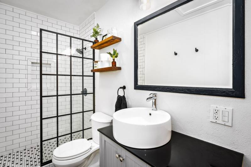 bathroom with white tile and black countertops