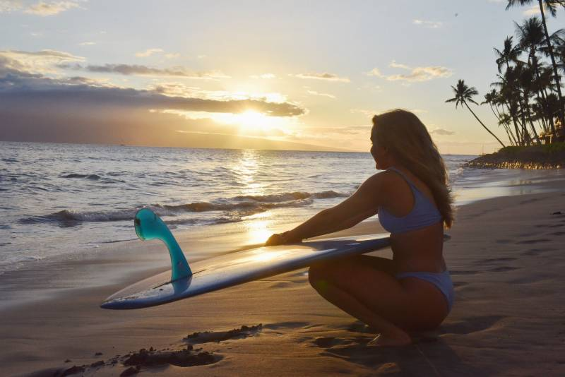 girl with surfboard on beach in west maui