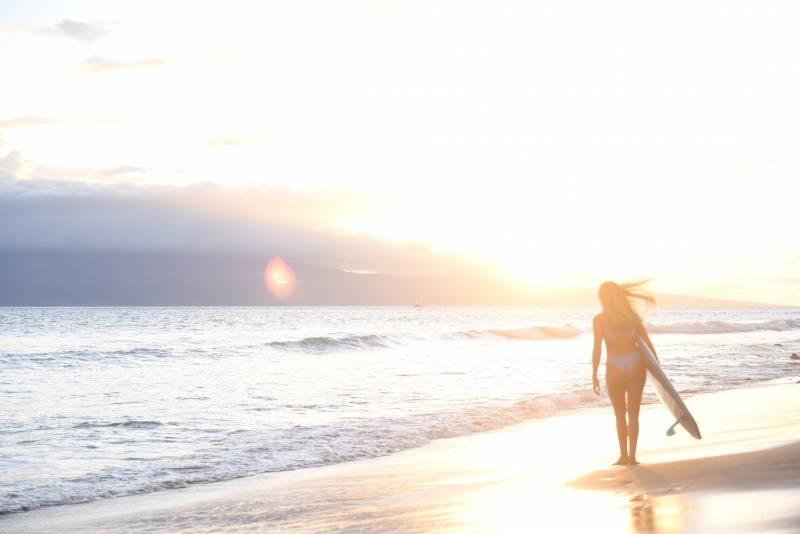 walking on beach during sunrise puamana maui