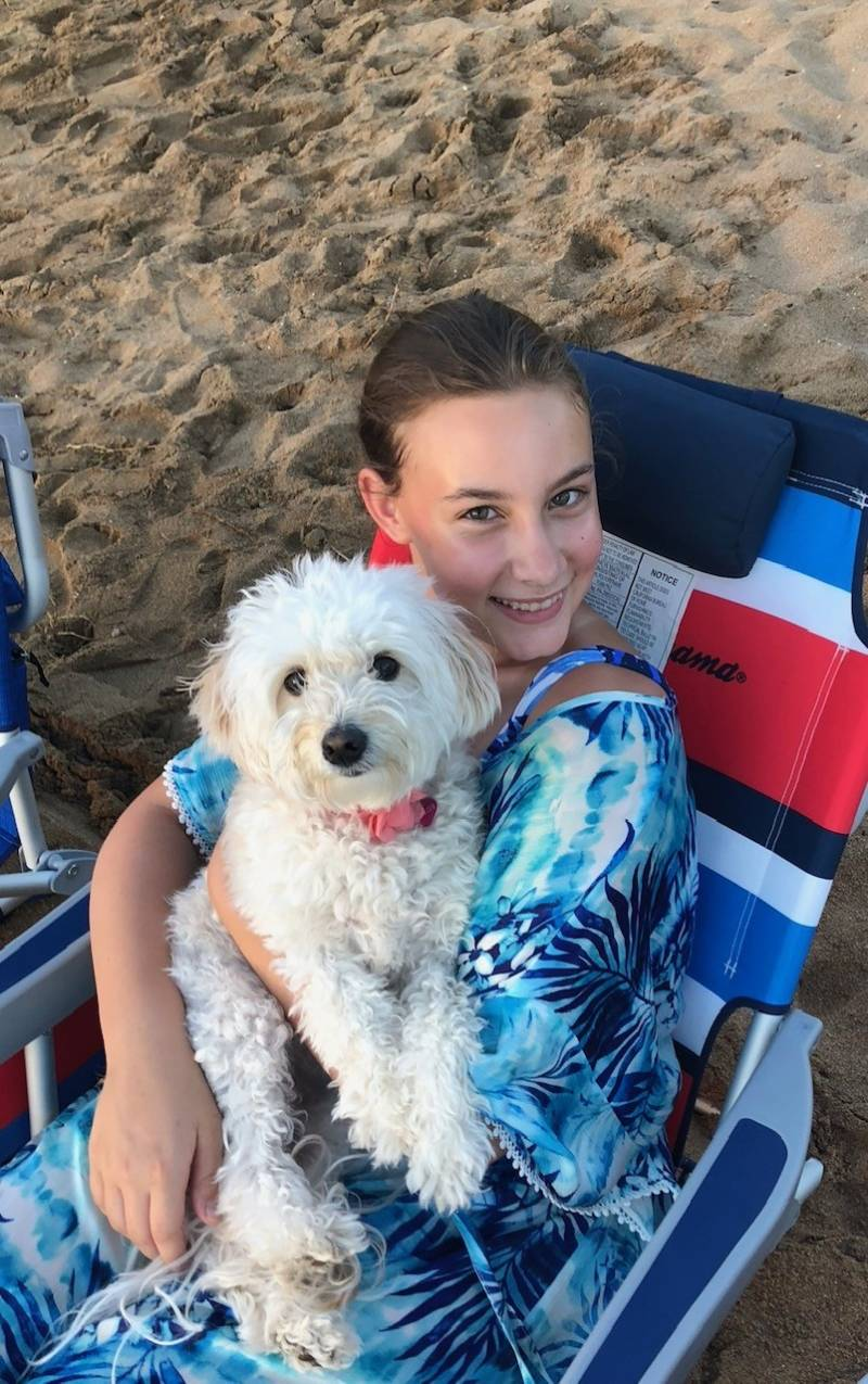girl with dog sitting on the beach